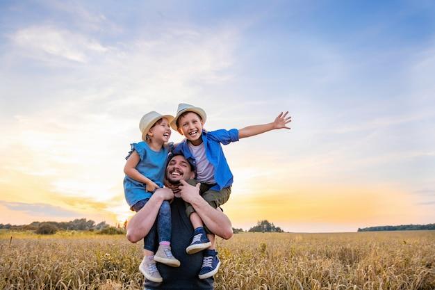 Отец держит двух своих детей в пшеничном поле
