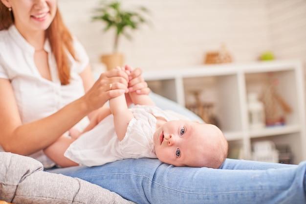 体操の赤ちゃん。その開発のための赤ちゃんと一緒に運動をしている女性。小さな新生児をマッサージします。