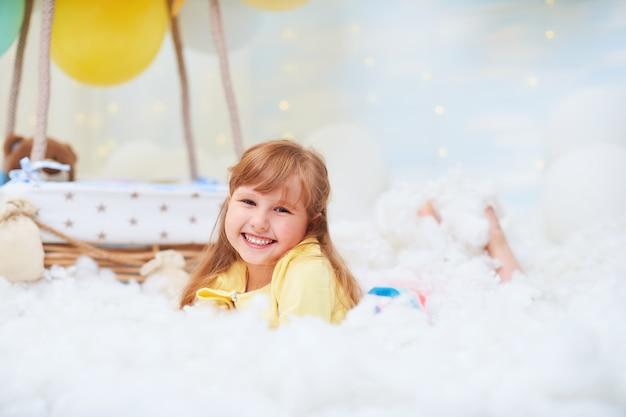 Портрет девочки лежал на облаке рядом с корзиной из воздушного шара в облаках, путешествовать и летать в мечтах.