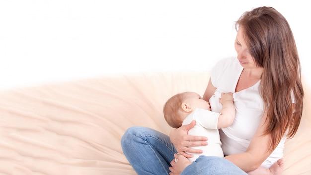 Молодая женщина кормит грудь ребенка, сидя на кровати. со свободным пространством для текста.