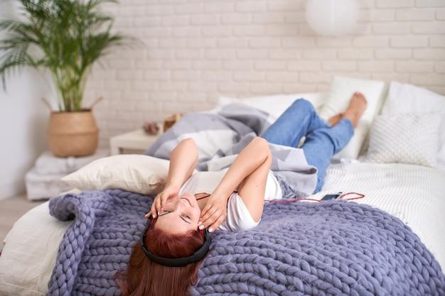 Девушка слушая к музыке в наушниках в кровати. светлая спальня утренний свет из окон