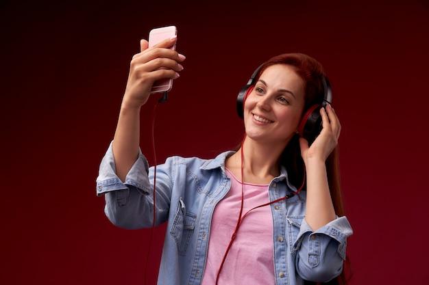 Привлекательная рыжая женщина радость, позитив, носить наушники, держа смартфон