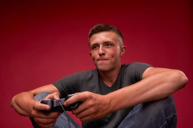 Подросток играет в видеоигры. молодой человек сидит м джойстик в руках.