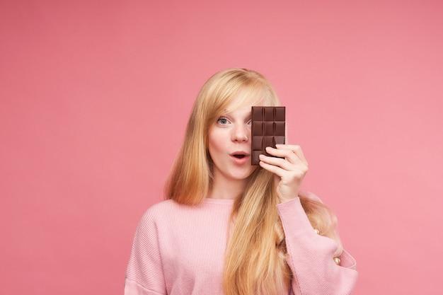 チョコレートと若い美しいブロンド。十代の少女はチョコレートをかみます。禁断のチョコレートを食べる誘惑。チョコレートバーを保持している陽気な肯定的な若い女の子。