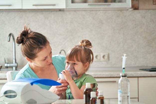 女性は自宅で子供を吸入します。彼の顔にネブライザーマスクをもたらします。薬の蒸気を吸い込みます。女の子はマスクを通して呼吸します。テーブルの上の薬。