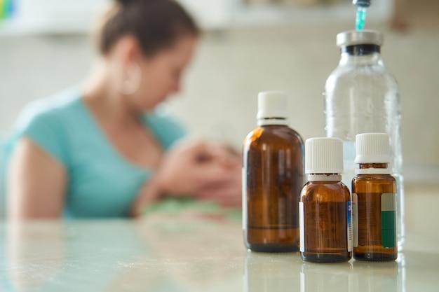 テーブルの上の薬。女性は子供を抱き、注意深く子供を彼女に押し付けます。病気で体調が悪い。薬瓶に焦点を当てています