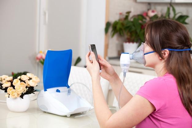 Молодая женщина делает ингаляции с помощью небулайзера в домашних условиях