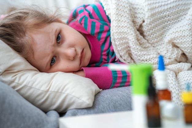 病気の少女は、毛布に包まれたソファーに横になっています。テーブルの薬。