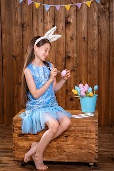 イースター、おめでとう!木製のたんすの後ろに座って、イースターエッグを着色するかわいい女の子。