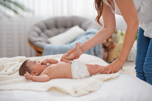 ベビーマッサージ。ママは体操をして、かわいい新生児をマッサージします。