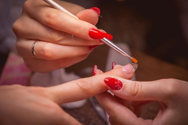 Маникюр. мастер сделать наращивание ногтей: нанесение белого геля на свободный край ногтя