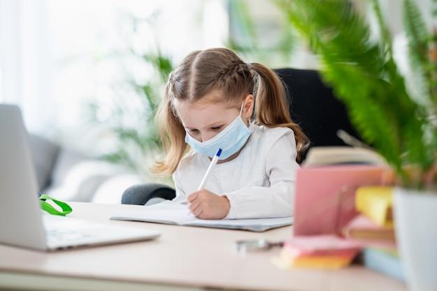 Милая маленькая девочка, делать домашнее задание, писать в блокноте, используя ноутбук, электронное обучение