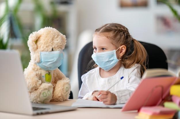 Маленькая девочка в маске, с мишкой, делает домашнее задание, пишет в тетради
