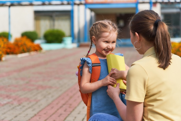 母親は子供を学校に連れて行く。