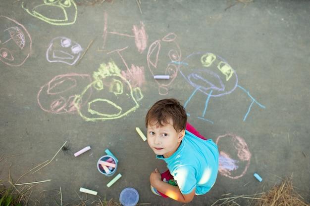 少年は歩道にチョークで描きます