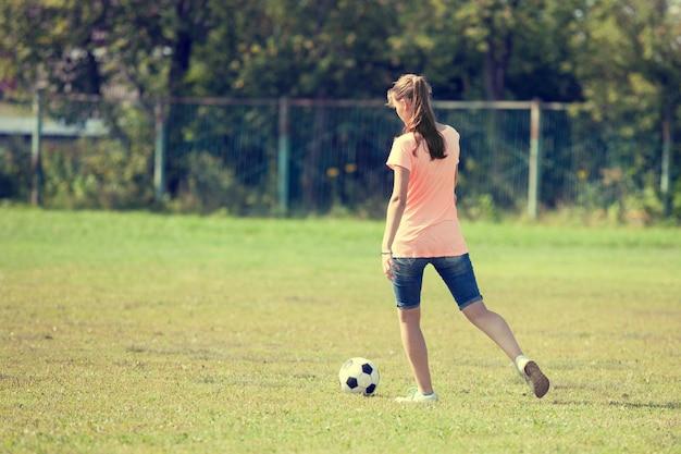 Спортсменка пинает мяч, играет в футбол.