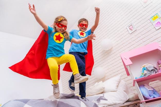 かわいい小さな女の子と男の子がベッドからジャンプして飛ぶ、スーパーヒーローをプレイ