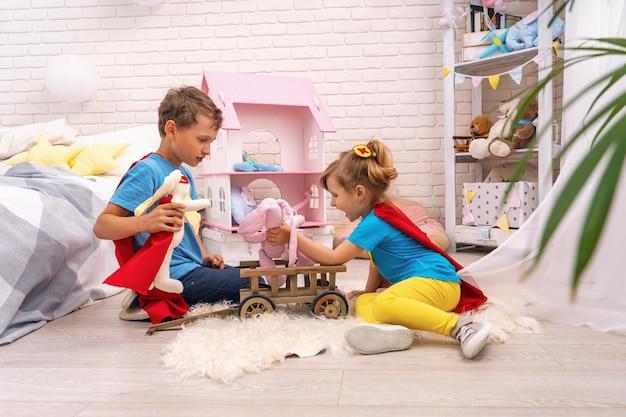 面白い子供たちは、子供部屋でスーパーヒーローのおもちゃで遊んでいます。