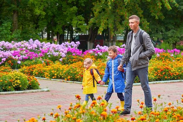 Счастливые дети смеются, бегут в школу, одетые в плащи с портфелем за рюкзаком.