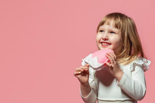 ピンクのサンゴの背景に幸せな赤ちゃん