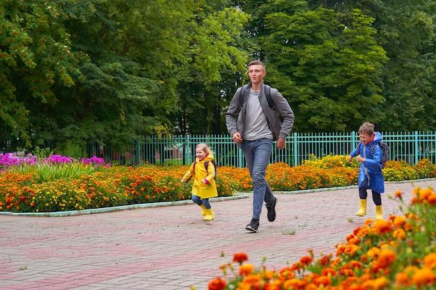 幸せな子供たちは、急いで笑い、バックパックの後ろにブリーフケースを着てレインコートを着て学校に走ります。
