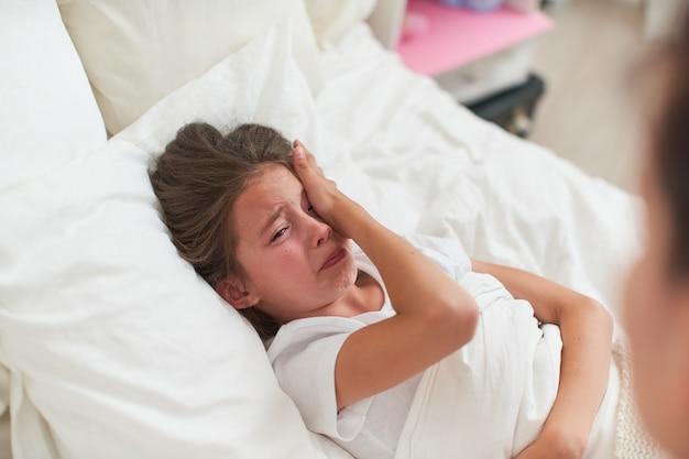 Маленький ребенок - девочка, лежащая в кровати и плача яростно. мать утешает ребенка.