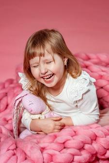 ピンクのサンゴの背景に幸せな赤ちゃんは驚きで見上げます。フリーテキストスペース。