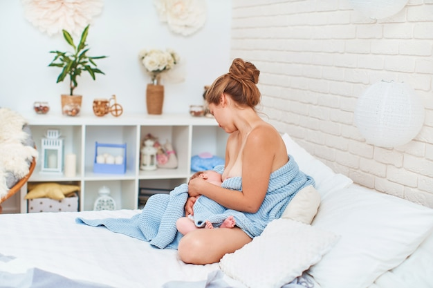 幸せな若い女性が座っていると彼女の赤ちゃんを抱き締める間母乳で育てる