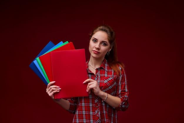 Предназначенная для подростков женщина студента изолированная на красной стене держа папки для исследования
