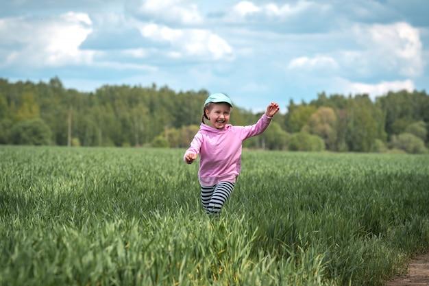 Смешная маленькая девочка бежит по полю с зелеными побегами пшеницы в сельской местности