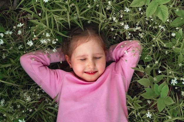 花の草原に横たわっているおさげ髪の笑顔の少女の肖像画