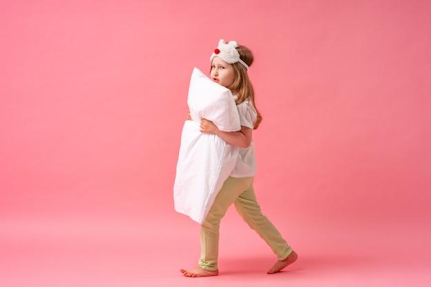 Веселая маленькая девочка в маске для сна смотрит из-за подушки