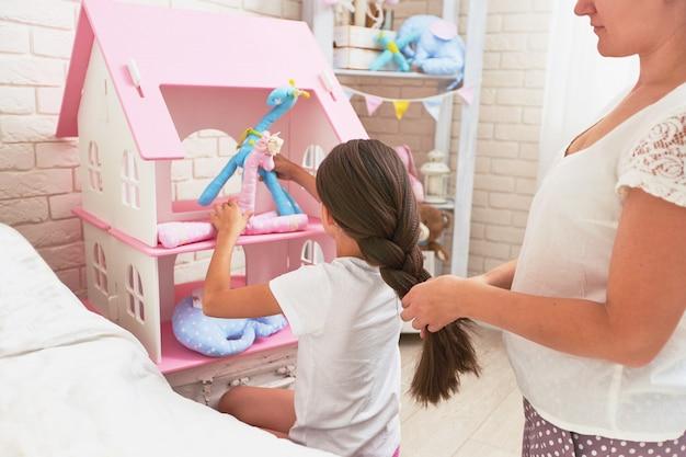 思いやりのある母親がおもちゃで遊んでいるときに娘の髪を編む
