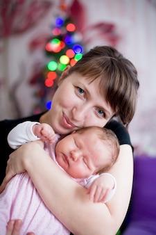 眠っている赤ちゃんを抱いて女性