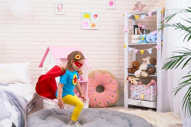 Привлекательная милая маленькая девочка прыгает с кровати, чтобы летать, когда она играет супергероя