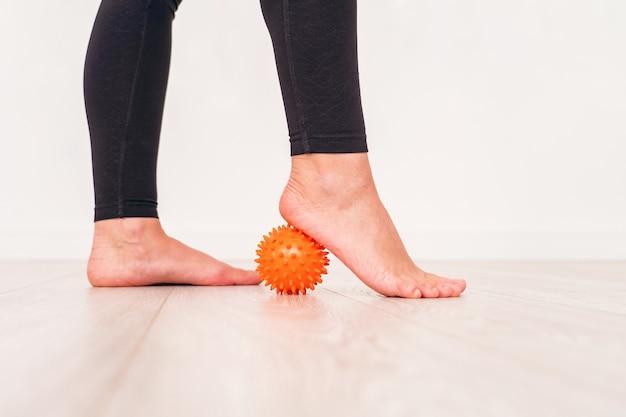 病院でストレスボールで運動する少女の低いセクション。足の下のマッサージボール。