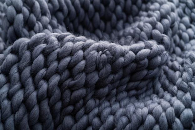 メリノウールの手作りニットの大きな毛布、極太の糸、トレンディなコンセプト。ニット毛布、メリノウールのクローズアップ。ベージュのスモーキーウール製のデザイナーブランケット