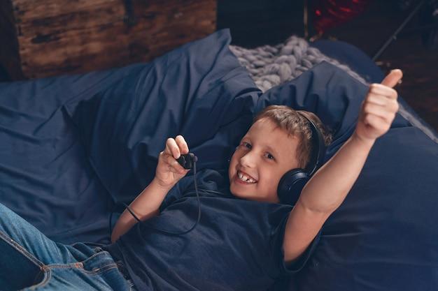 笑みを浮かべて少年はヘッドフォンで音楽を聴いて、ベッドに横たわって、承認のジェスチャー