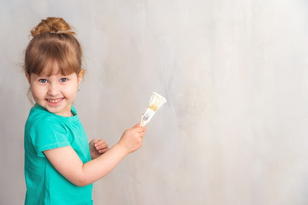 子供は白いペイントブラシで壁を塗る