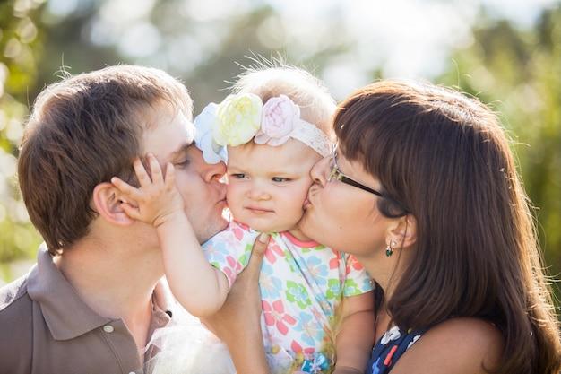 Счастливые родители целуют своего ребенка в щеку в парке
