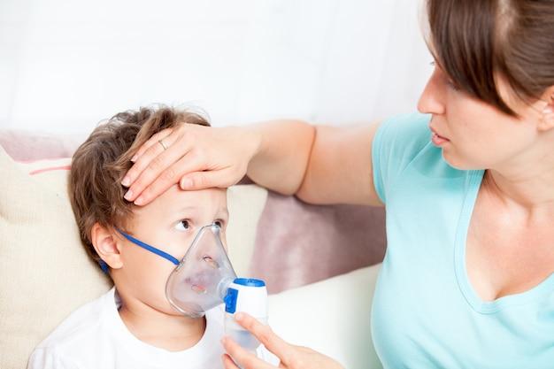 ネブライザーの息子と吸入を行う若い女性と彼の額に触れる