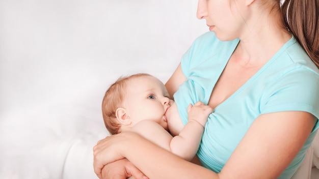 Молодая женщина кормит грудью ребенка, сидящего в кресле