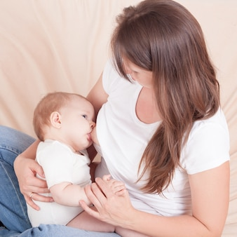 若い女性がベッドの上に座って赤ちゃんの胸に餌をやる