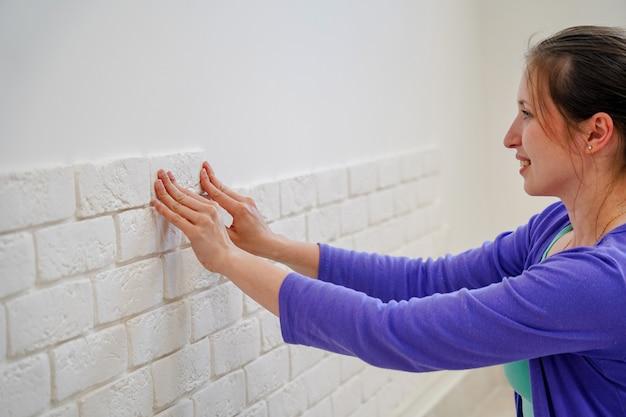 女の子は壁に装飾的なレンガをマウントします