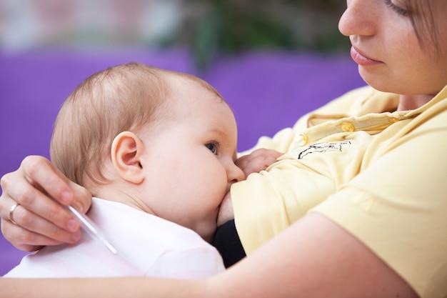 若い女性が赤ちゃんに授乳し、体温を測定する