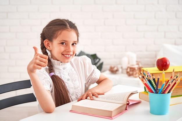鉛筆でテーブルに座ってうれしそうな少女