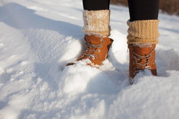 雪の中に立っている冬の靴は、靴下を編んだ