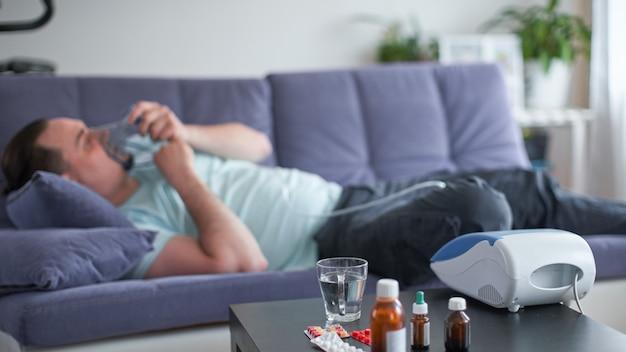 彼がぼやけているソファに横たわっている病人