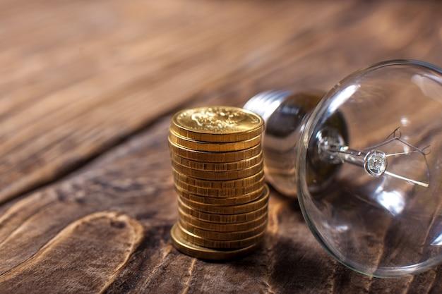 灰色の背景上のコインと古い透明なガラス電球