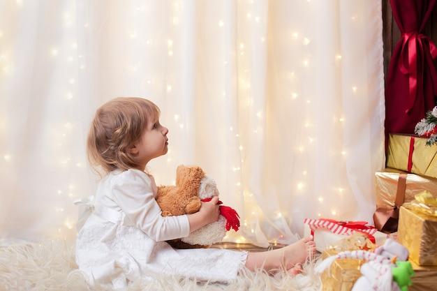 クリスマスツリーを見て座っている女の子